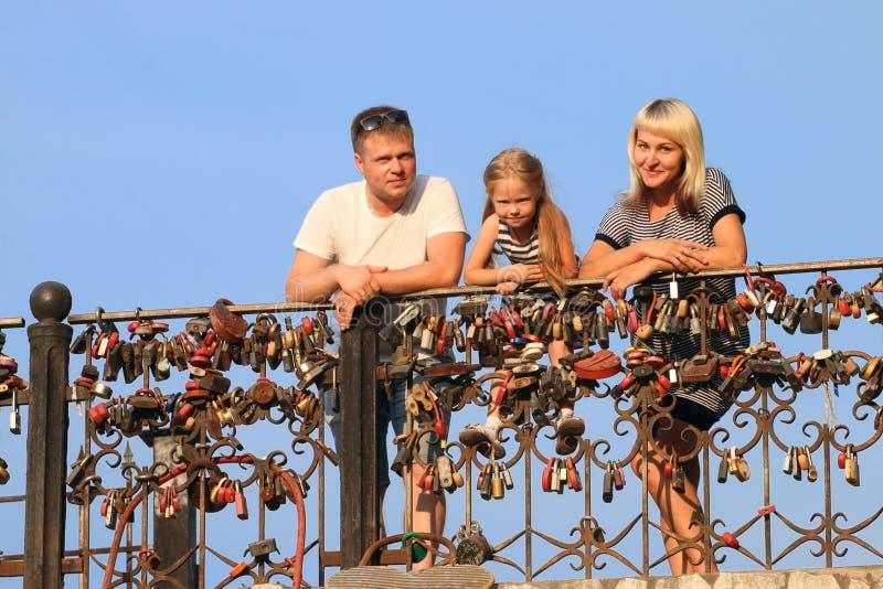 Μητέρα, πατέρας, λίγη στάση κορών κοντά στο κιγκλίδωμα με το lo στοκ εικόνες