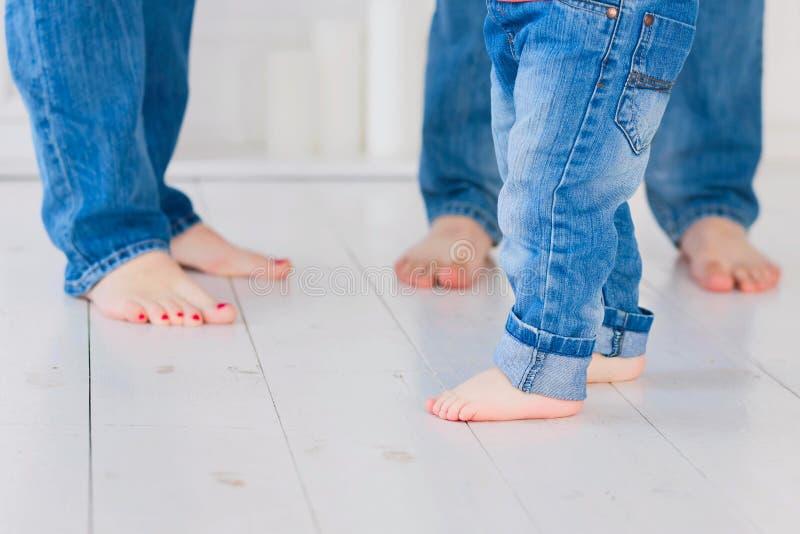 Μητέρα, πατέρας και λίγο παιδί που φορούν το τζιν παντελόνι, χωρίς παπούτσια FO στοκ φωτογραφία