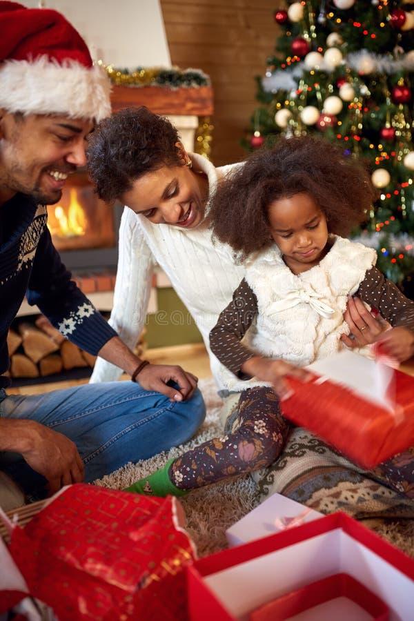 Μητέρα, πατέρας και κόρη στο ανοίγοντας παρόν πρωινού Χριστουγέννων στοκ φωτογραφία