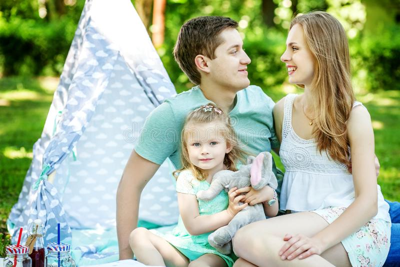 Μητέρα, πατέρας και λίγη κόρη σε ένα πικ-νίκ στο πάρκο _ στοκ εικόνα