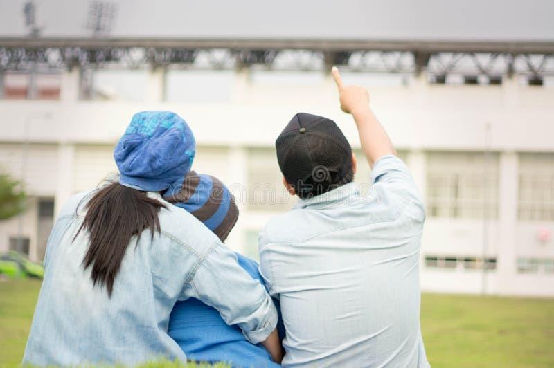 Μητέρα πατέρων, γιος στο πάρκο, αγωνιστικός χώρος ποδοσφαίρου και χορτοτάπητας στοκ εικόνες