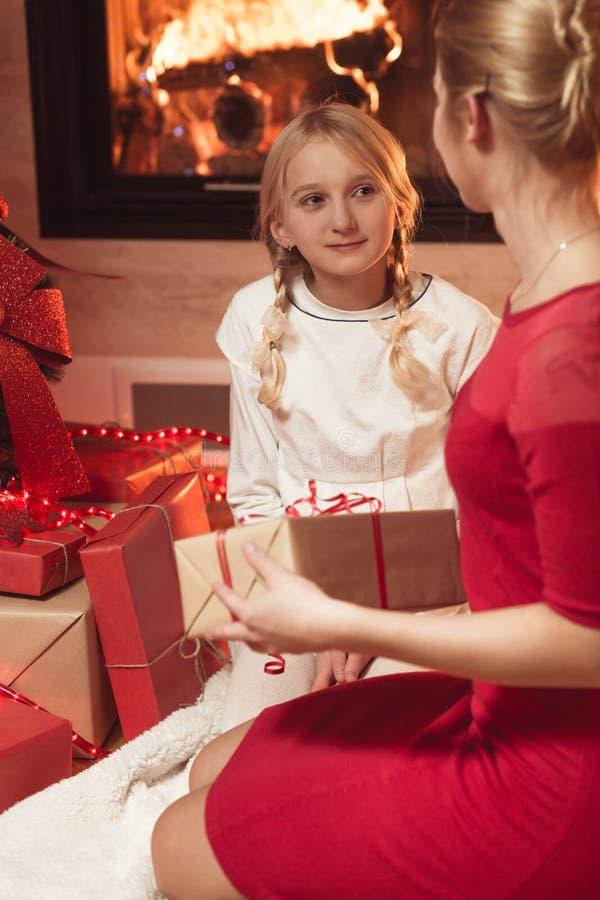 Μητέρα που δίνει το χριστουγεννιάτικο δώρο κορών στοκ εικόνα με δικαίωμα ελεύθερης χρήσης