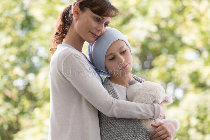 Μητέρα που αγκαλιάζει τη λυπημένη κόρη με τον καρκίνο στοκ εικόνες