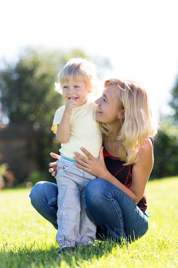 Μητέρα που αγκαλιάζει το παιδί της στον πράσινο χορτοτάπητα Χαμογελώντας αγόρι μικρών παιδιών με το mom του Ηλιόλουστη ημέρα υπαί στοκ εικόνες με δικαίωμα ελεύθερης χρήσης