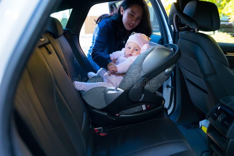Μητέρα που βάζει το μωρό της στην καρέκλα μωρών στοκ εικόνες