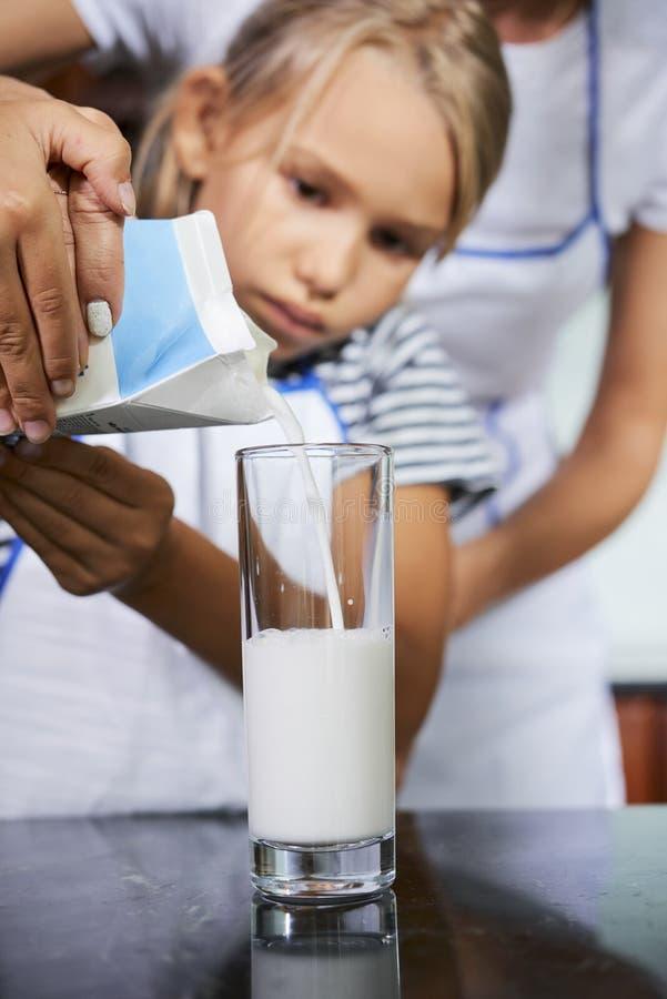 Μητέρα που βοηθά την κόρη για να γεμίσει το γυαλί με το γάλα στοκ φωτογραφία με δικαίωμα ελεύθερης χρήσης