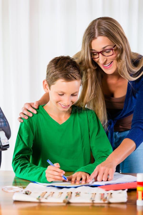 Μητέρα που βοηθά το γιο με την ανάθεση εργασίας στοκ φωτογραφία με δικαίωμα ελεύθερης χρήσης