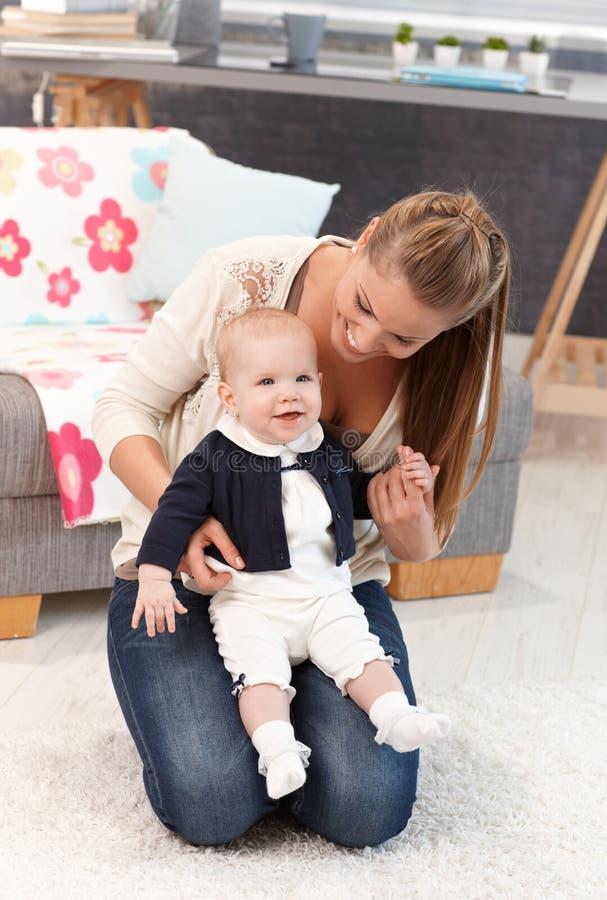 Μητέρα που γονατίζει στο πάτωμα με το κοριτσάκι στην περιτύλιξη στοκ φωτογραφίες