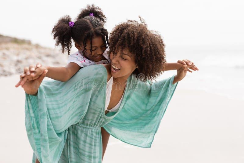 Μητέρα που δίνει piggyback το γύρο στην κόρη της στην παραλία στοκ φωτογραφίες