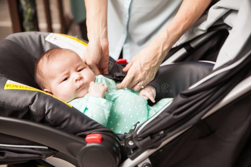 Μητέρα που εξασφαλίζει το μωρό στο μεταφορέα στοκ εικόνα