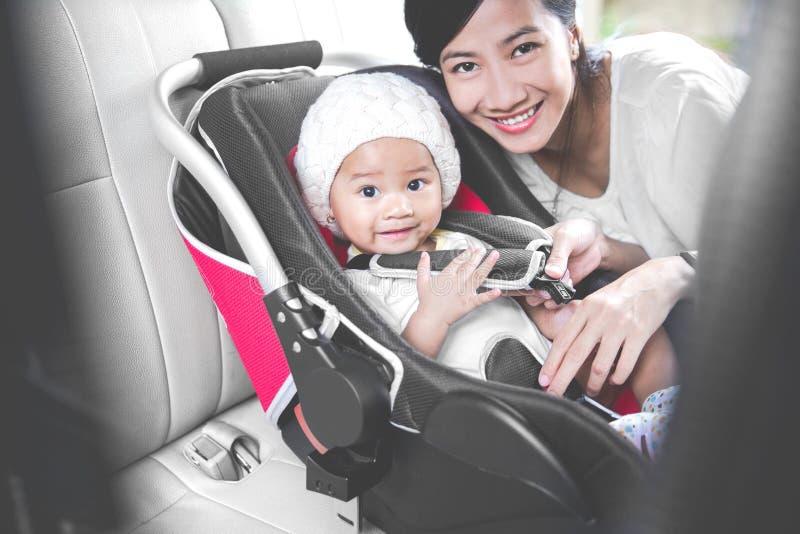 Μητέρα που εξασφαλίζει το μωρό της στο κάθισμα αυτοκινήτων στο αυτοκίνητό της στοκ φωτογραφία με δικαίωμα ελεύθερης χρήσης