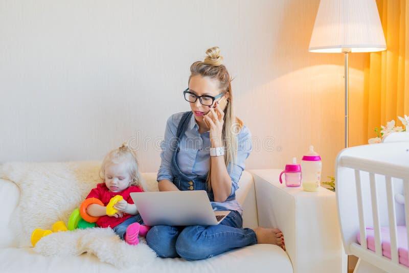 Μητέρα που εργάζεται στο lap-top στο σπίτι στοκ φωτογραφία
