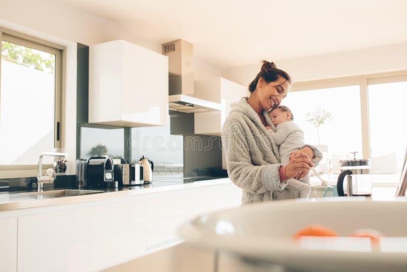 Μητέρα που κατασκευάζει τα τρόφιμα για το γιο της στην κουζίνα στοκ εικόνες
