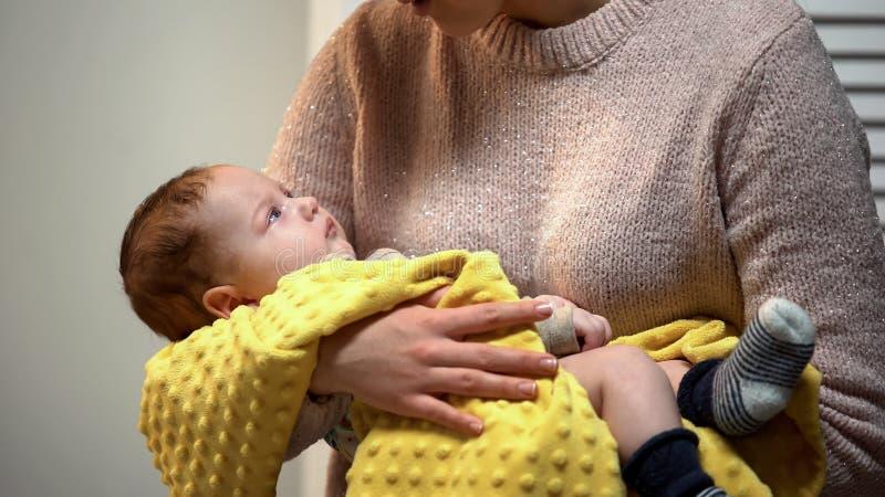 Μητέρα που κρατά λίγο νυσταλέο αγοράκι και που εξετάζει χαριτωμένο νεογέννητο, συγκίνηση αγάπης στοκ φωτογραφία με δικαίωμα ελεύθερης χρήσης