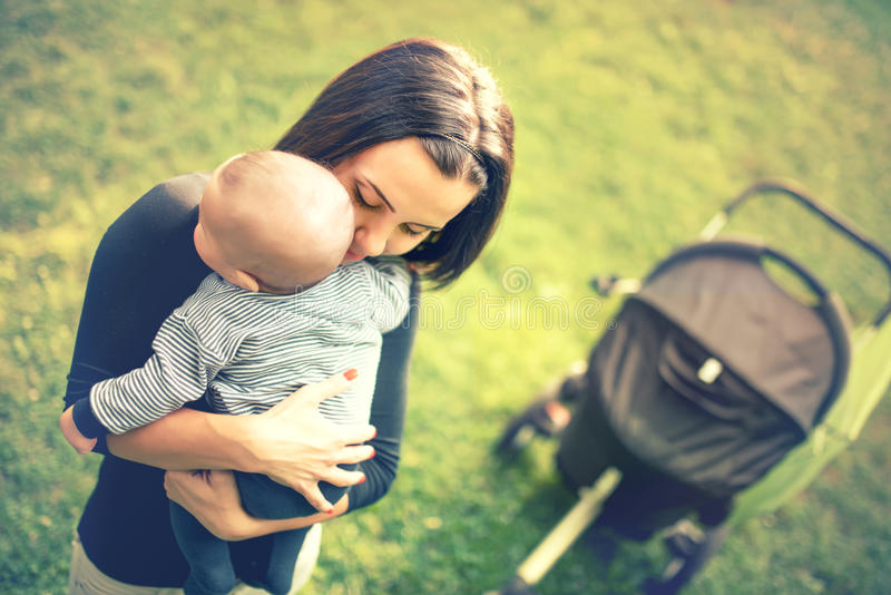 Μητέρα που κρατά το νεογέννητο γιο στα χέρια Αγάπη του χεριού μητέρων που κρατά το χαριτωμένο παιδί μωρών ύπνου νεογέννητο στο πά στοκ φωτογραφίες