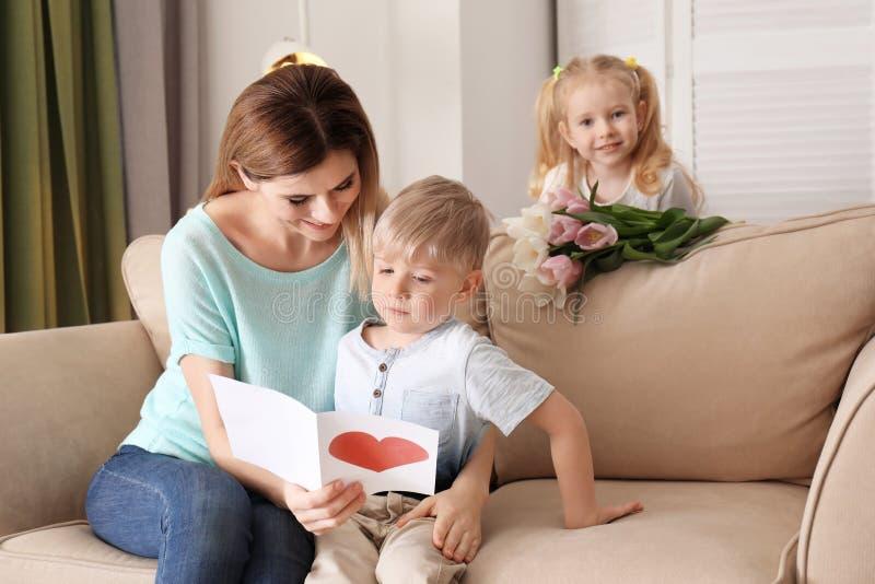 Μητέρα που λαμβάνει τη ευχετήρια κάρτα και τα λουλούδια από τα χαριτωμένα μικρά παιδιά της στο σπίτι στοκ εικόνα