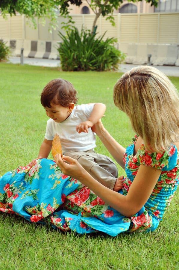Μητέρα που παίζει με την λίγο γιο στη χλόη στοκ φωτογραφίες με δικαίωμα ελεύθερης χρήσης