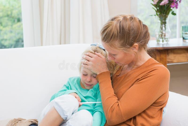 Μητέρα που παίρνει τη θερμοκρασία της άρρωστης κόρης στοκ εικόνες