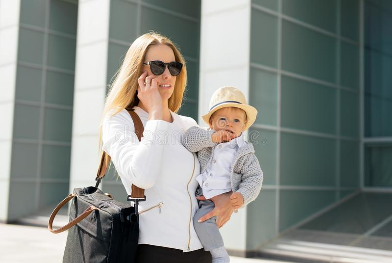 Μητέρα που πηγαίνει να εργαστεί και που μιλά στο τηλέφωνο με το μωρό στα χέρια της στοκ εικόνα