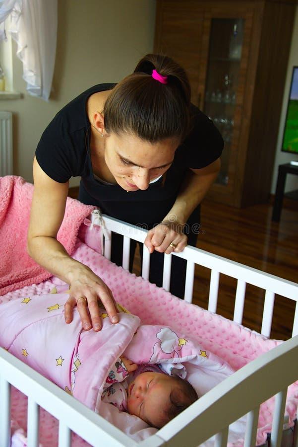 Μητέρα που προσέχει το νεογέννητο παιδί ύπνου της στοκ εικόνες