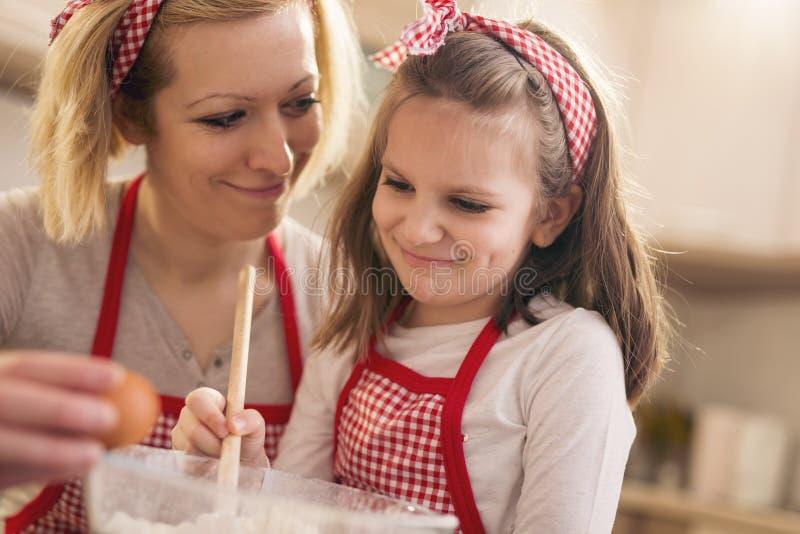 Μητέρα που προσθέτει ένα αυγό ενώ η κόρη ζυμώνει τη ζύμη στοκ εικόνες