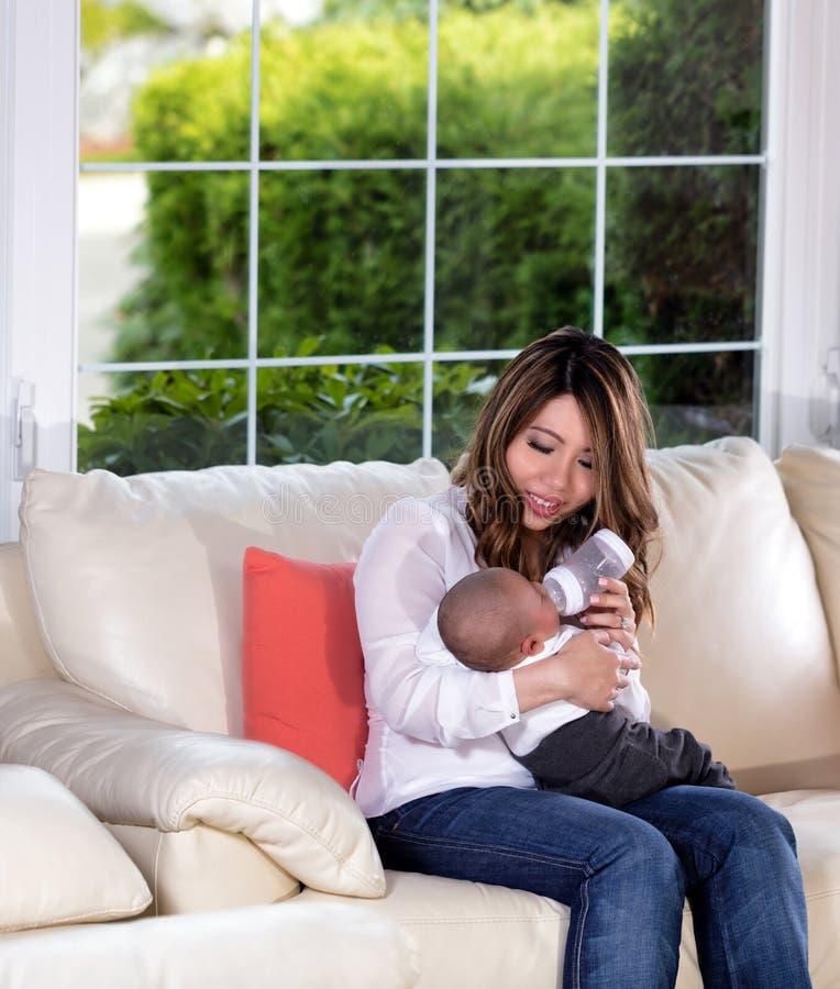Μητέρα που ταΐζει το γιο νηπίων της στον άσπρο καναπέ στοκ φωτογραφία με δικαίωμα ελεύθερης χρήσης