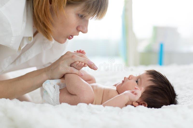 Μητέρα που τρίβει ήπια τα πόδια μωρών της ` s στοκ εικόνα