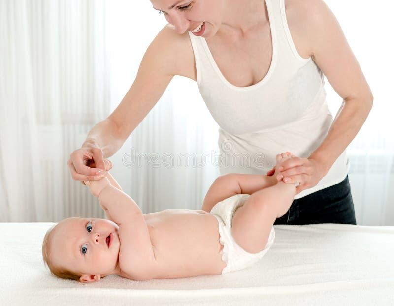 Μητέρα που τρίβει το μωρό νηπίων της στοκ εικόνες