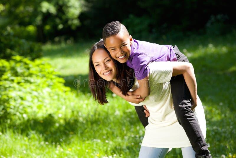 Μητέρα που χαμογελά υπαίθρια με τον ευτυχή γιο στοκ εικόνα