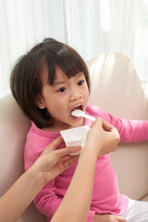 Μητέρα συγκομιδών που ταΐζει λίγο εθνικό κορίτσι στοκ φωτογραφία