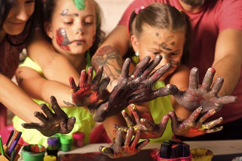 Μητέρες, πατέρες, χέρια κοριτσιών που χρωματίζονται με τα χρώματα στοκ εικόνες
