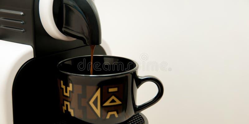 Μηχανή καφέ που χύνει ισχυρό να φανεί φρέσκος καφές σε ένα τακτοποιημένο κεραμικό φλυτζάνι στοκ εικόνες