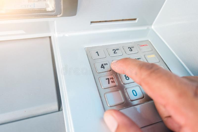 Μηχανή κινηματογραφήσεων σε πρώτο πλάνο ATM και χέρι δάχτυλων που πληκτρολογεί τον πιέζοντας προσωπικό κωδικό για την απόσυρση τω στοκ φωτογραφίες