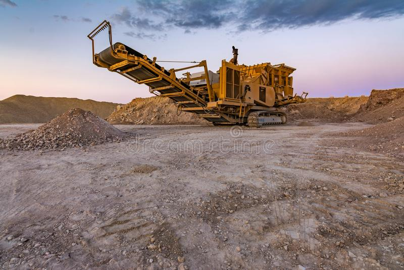 Μηχανή πέτρινων θραυστήρων σε ένα λατομείο ή ένα open-pit ορυχείο, για να μετασχηματίσει στο αμμοχάλικο στοκ φωτογραφία