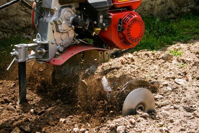 Μηχανή που οργώνει το έδαφος που κάνει το άλμα πετρών και υπολειμμάτων στοκ εικόνες