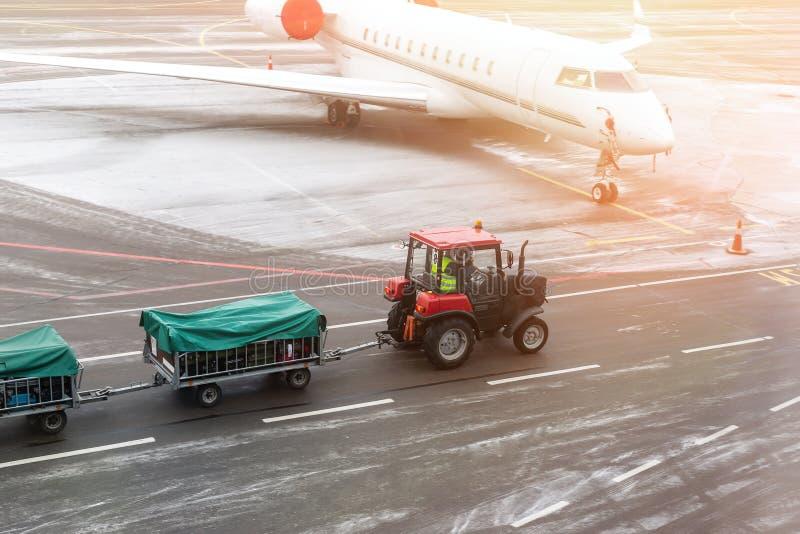 μηχανή τρακτέρ φορτίου φορτίου που παραδίδει τα κάρρα αποσκευών στο αεροπλάνο στον αερολιμένα Μεταφορέας και υπηρεσία αερολιμένων στοκ φωτογραφία με δικαίωμα ελεύθερης χρήσης
