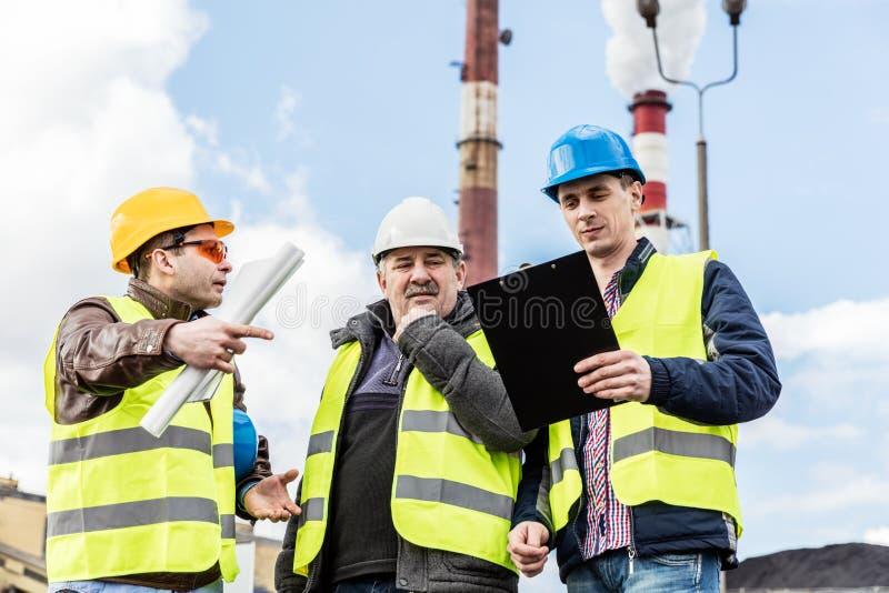Μηχανικοί κατασκευής που εξετάζουν το θερμοηλεκτρικό σταθμό παραγωγής ηλεκτρικού ρεύματος στοκ εικόνες