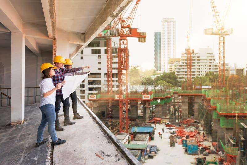 3 μηχανικοί κατασκευής που εργάζονται μαζί στο εργοτάξιο οικοδομής δ στοκ φωτογραφία