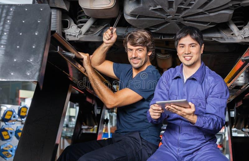 Μηχανικοί με την ψηφιακή ταμπλέτα που λειτουργεί κάτω από ανυψωμένος στοκ εικόνες