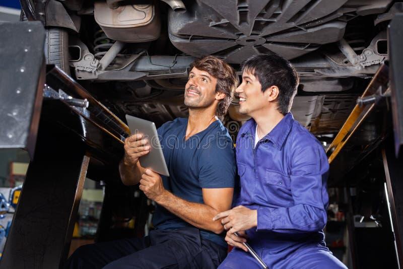 Μηχανικοί με την ψηφιακή ταμπλέτα που εξετάζουν κάτω από το αυτοκίνητο στοκ φωτογραφία με δικαίωμα ελεύθερης χρήσης