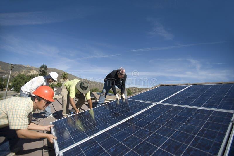 Μηχανικοί που ανυψώνουν το βαρύ ηλιακό πλαίσιο ενάντια στο μπλε ουρανό στοκ φωτογραφίες με δικαίωμα ελεύθερης χρήσης