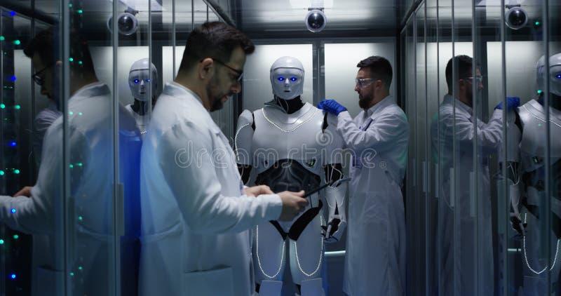 Μηχανικοί που εξετάζουν στους ελέγχους ρομπότ στοκ φωτογραφίες με δικαίωμα ελεύθερης χρήσης