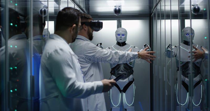 Μηχανικοί που εξετάζουν στους ελέγχους ρομπότ στοκ φωτογραφία
