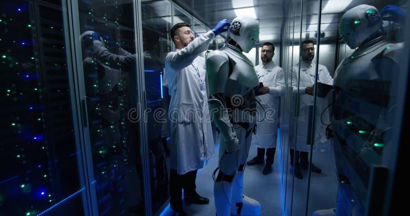 Μηχανικοί που εξετάζουν στους ελέγχους ρομπότ στοκ φωτογραφία με δικαίωμα ελεύθερης χρήσης