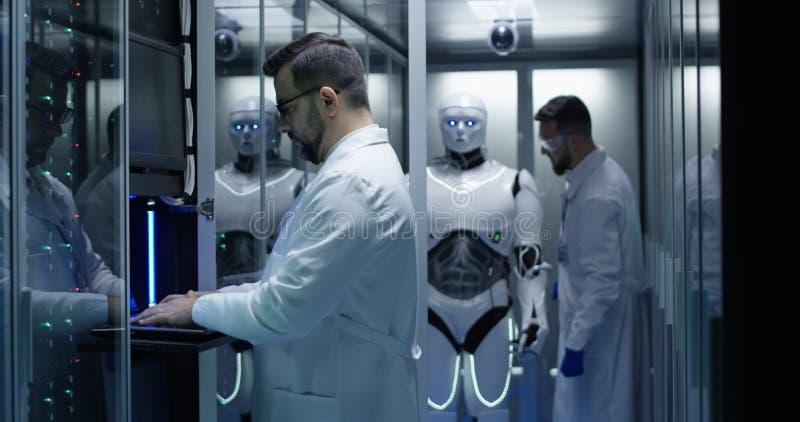 Μηχανικοί που εξετάζουν στους ελέγχους ρομπότ στοκ εικόνες