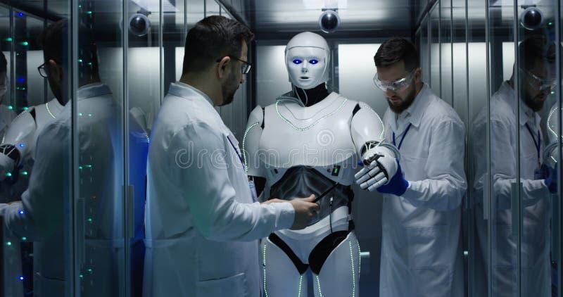 Μηχανικοί που εξετάζουν στους ελέγχους ρομπότ στοκ φωτογραφίες