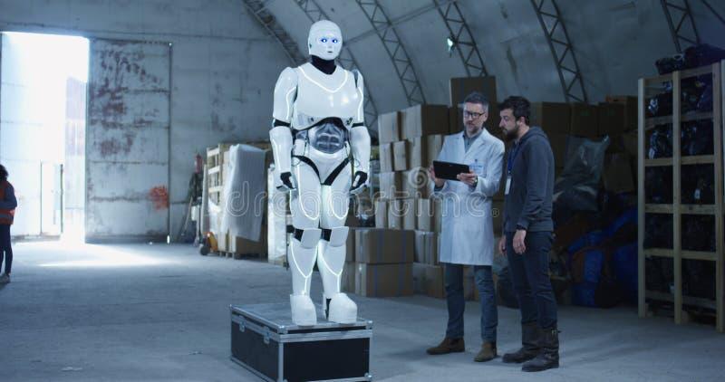 Μηχανικοί που εξετάζουν το ρομπότ σε μια αποθήκη εμπορευμάτων στοκ εικόνες με δικαίωμα ελεύθερης χρήσης