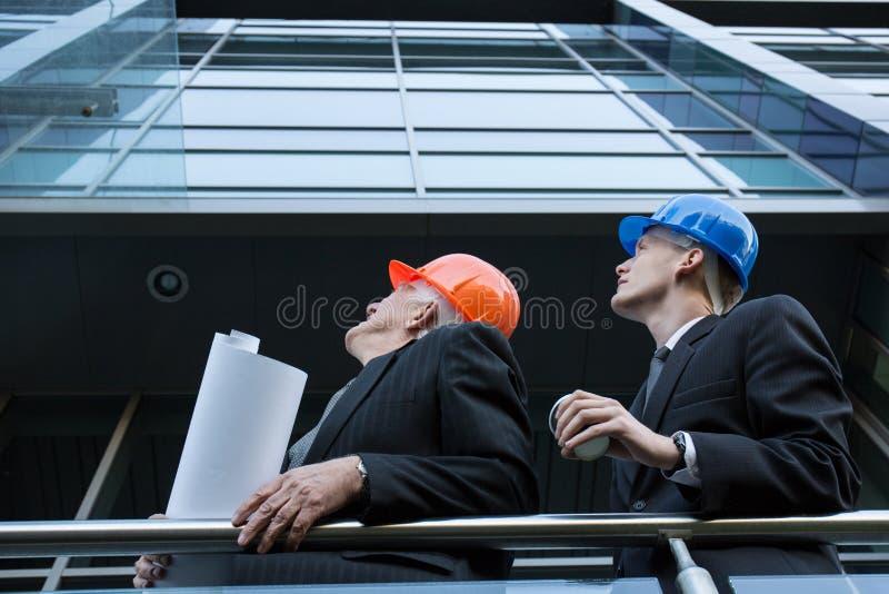 Μηχανικοί που εποπτεύουν το εργοτάξιο οικοδομής στοκ εικόνες