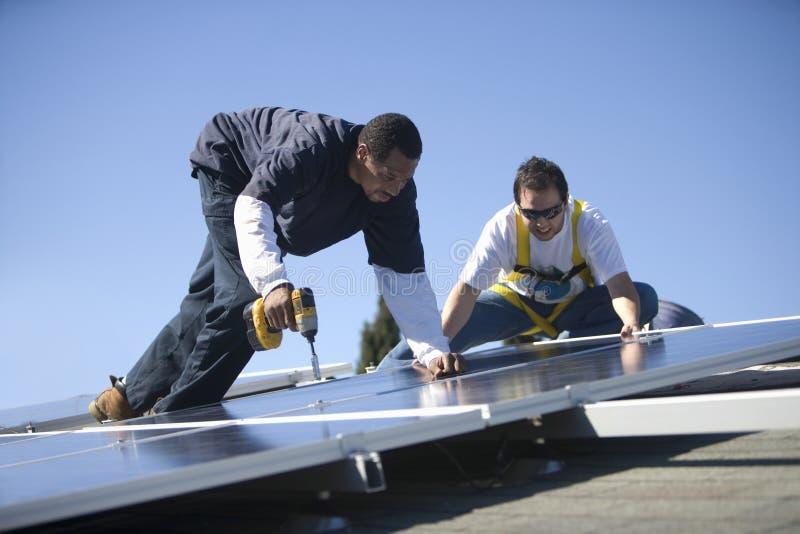 Μηχανικοί που εργάζονται στα ηλιακά πλαίσια ενάντια στον ουρανό στοκ φωτογραφία με δικαίωμα ελεύθερης χρήσης