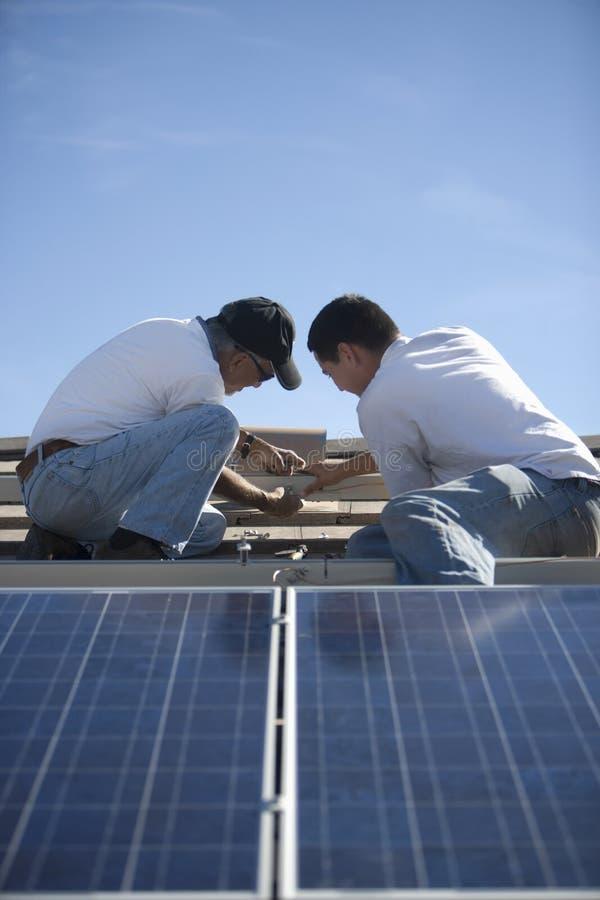 Μηχανικοί που εργάζονται στην ηλιακή ξυλεπένδυση στη στέγη στοκ εικόνες με δικαίωμα ελεύθερης χρήσης